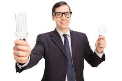 Yong man in a black suit holding two light bulbs Royalty Free Stock Images
