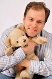 Yong man hugging teddybear. Isolated on light grey background Stock Photo