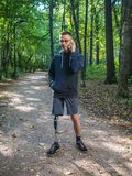 Yong man with prosthetic leg talking on the phone. While on the walk in a city park stock images