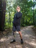 Yong man with prosthetic leg talking on the phone. While on the walk in a city park royalty free stock photo