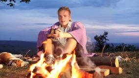 Yong man sit next to a campfire with warm drinks and watch on campfire. stock footage