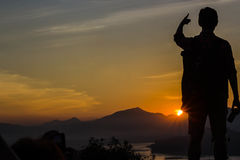 Yong man standing on sunset backdrop Royalty Free Stock Photos