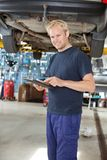 Yong mechanic with digital tablet. Portrait of young mechanic standing and using digital tablet in his auto repair shop stock image