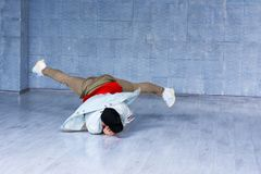 Yong modern style dancer in movement. Yong man in trendy clothes dancing brak dance on grey floor. Street dance concept royalty free stock photo