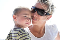 Yong mother and his baby boy outdoor, natural light, sunglasses Stock Photos