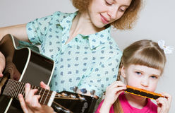 Yong mother a nd her  pretty daughter playing on  musical instru Stock Image