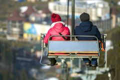 Yong pair riding chair lift on vacation in mountains.  Stock Photos