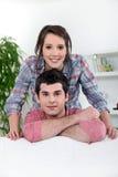 Yong par på en sofa Fotografering för Bildbyråer