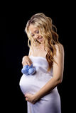 Yong pregnant woman play with baby's bootee. Yong pregnant woman in white silk play with baby's bootee on belly Stock Photography
