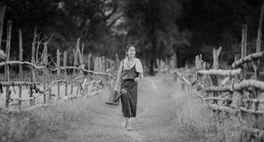 Yong woman in farmer suit on the way Royalty Free Stock Photography