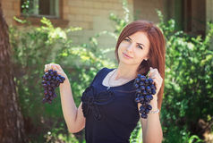 Yong woman holding grapes bunches Stock Photo