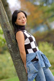 Yong woman leaning against a tree. Modern young woman posing for picture Stock Photo