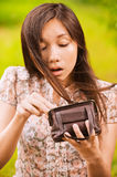 Yong woman looking in her little. Portrait of young surprised woman looking into her little bag at summer green park Royalty Free Stock Image