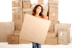 Yong woman moving holding a blank box with boxes stacked in the background Stock Photo