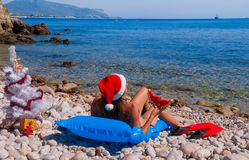 Yong woman in Santa hat on the beach Royalty Free Stock Photo