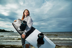 Yong woman standing on the shore with wakeboard Royalty Free Stock Images