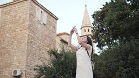 Yong Woman Taking Pictures By Smartphone Femme élégante de voyageur d'été avec le téléphone dehors dans la ville européenne, viei Images stock