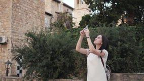 Yong Woman Taking Pictures By Smartphone Mujer elegante del viajero del verano con el teléfono al aire libre en la ciudad europea almacen de video