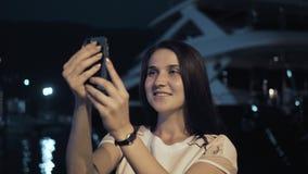 Yong Woman Taking Pictures By Smartphone Mulher à moda do viajante do verão com telefone fora na cidade europeia, baía da noite Fotos de Stock Royalty Free