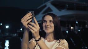 Yong Woman Taking Pictures By Smartphone Mulher à moda do viajante do verão com telefone fora na cidade europeia, baía da noite Fotos de Stock