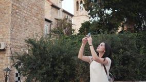 Yong Woman Taking Pictures By Smartphone Mulher à moda do viajante do verão com telefone fora na cidade europeia, cidade velha Foto de Stock Royalty Free