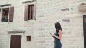 Yong Woman Taking Pictures By Smartphone Mulher à moda do viajante do verão com telefone fora na cidade europeia, cidade velha Fotos de Stock Royalty Free