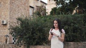 Yong Woman Taking Pictures By Smartphone Mulher à moda do viajante do verão com telefone fora na cidade europeia, cidade velha Imagem de Stock Royalty Free