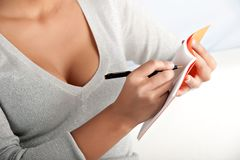 Yong woman writes with ballpoint pen Royalty Free Stock Photos