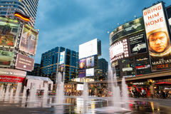 Yonge and Dundas square illuminated at dusk. Toronto, Canada - September 12, 2015: People shopping and relaxing at Yonge and Dundas Square in Toronto at dusk Royalty Free Stock Photography