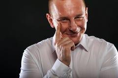 Yonug man som tänker med fingret nära hans le för framsida Arkivfoto