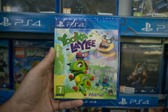 Yooka Laylee. Bratislava, Slovakia, circa april 2017: Man holding Yooka Laylee videogame on Sony Playstation 4 console in store Royalty Free Stock Images
