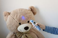 Young boy is looking after his sick teddy bear. Boy is measuring temperature on its forehead with modern digital thermometer. - stock photography