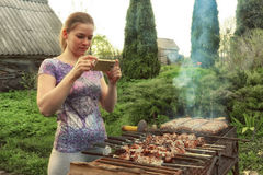 Yooung woman cooks meat on barbecue grill Stock Photo