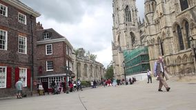 YORK, ENGLAND, JUNE 22, 2015: visitors walking along old streets. Visitors walking along old streets in front of York Minster, England stock video footage