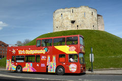 York sightseeing tour bus waits by Cliffords's tower a stone monument in York UK. A York tour bus waits for tourists below Cliffords's tower which is a stone Royalty Free Stock Photos