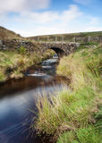 Yorkshire dales moorland packhorse bridge. A small moorland stream running smoothly under a stone packhorse bridge in the yorkshire dales Stock Images
