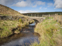 Yorkshire dales moorland packhorse bridge. A small moorland stream running smoothly under a stone packhorse bridge in the yorkshire dales Stock Image