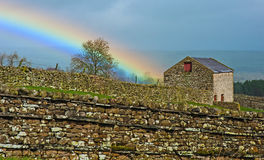 Yorkshire Dales in the rain. Rainbow over barn and typical stone walls in Yorkshire Dales near Grassington stock photography
