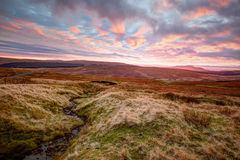 Yorkshire Dales At Sunset. Sunset view across moorland to the Pennines in the Yorkshire Dales. The distinctive, plateaued peak of Ingleborough, one of the famous Stock Images