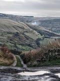 Yorkshire-Heidemoor im Winterweg und in den Steinwänden Stockfotos