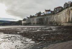 Yorkshire, Inglaterra, baía do ` s de Robin Hood - o penhasco e as casas imagem de stock