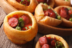 Yorkshire pudding filled with sausages and vegetables closeup. h Stock Photos