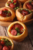 Yorkshire puddings stuffed with sausages close-up. Vertical Stock Image