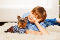 Yorkshire Terrier i sweater med pojken på matta arkivbilder