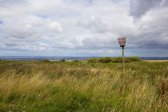 Yorkshire wolds beacon. An ornamental beacon amogst wild grasses and wildflowers with yorkshire wolds scenery under a blue summer sky with white clouds Stock Photos