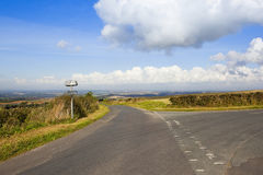 Yorkshire wolds road. A hilltop road in the yorkshire wolds with a sign post and views of patchwork fields under a blue sky with fluffy white clouds in autumn Royalty Free Stock Images