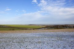Snowy winter landscape with farmland and village Royalty Free Stock Photos