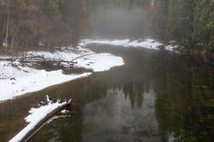 Yosemite в зиме с рекой Merced пропуская спокойно через снежный лес стоковое фото