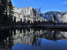 Yosemite Falls och granitberg reflekterat i den Merced floden Arkivbild