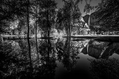 Yosemite Falls reflexion i den svartvita Merced floden Fotografering för Bildbyråer